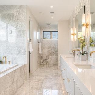 Diseño de cuarto de baño principal, clásico renovado, de tamaño medio, con armarios con paneles lisos, puertas de armario blancas, bañera encastrada, baldosas y/o azulejos blancos, lavabo bajoencimera, ducha empotrada, paredes blancas, suelo de mármol, encimera de cuarzo compacto y encimeras blancas
