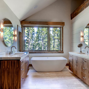 Mountain style freestanding bathtub photo in Denver with an undermount sink, flat-panel cabinets, dark wood cabinets and gray walls