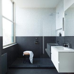 Ejemplo de cuarto de baño principal, moderno, de tamaño medio, con armarios con paneles lisos, puertas de armario blancas, ducha empotrada, baldosas y/o azulejos negros, baldosas y/o azulejos grises, baldosas y/o azulejos en mosaico, paredes multicolor, suelo con mosaicos de baldosas, lavabo bajoencimera, encimera de mármol, suelo negro, ducha abierta y encimeras grises