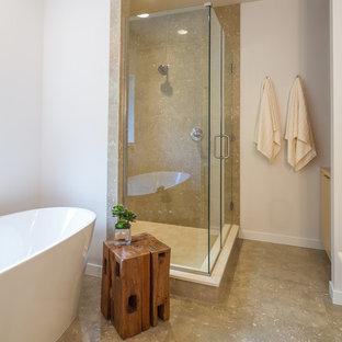 Foto di una stanza da bagno padronale minimalista di medie dimensioni con ante lisce, ante in legno chiaro, vasca freestanding, WC a due pezzi, piastrelle verdi, piastrelle in pietra, pareti bianche, pavimento in pietra calcarea, lavabo sottopiano e top in pietra calcarea