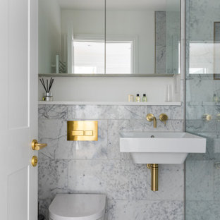 This is an example of a small classic shower room bathroom in London with an alcove bath, an alcove shower, a wall mounted toilet, grey tiles, a wall-mounted sink, grey floors, a hinged door and a single sink.