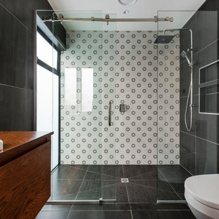 Modernes Duschbad mit flächenbündigen Schrankfronten, dunklen Holzschränken, Duschnische, Wandtoilette mit Spülkasten, schwarz-weißen Fliesen, weißer Wandfarbe, Einbauwaschbecken, schwarzem Boden und Schiebetür-Duschabtrennung in Auckland