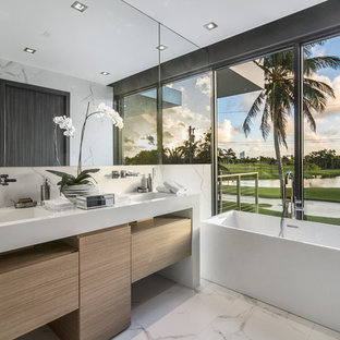Inspiration for a contemporary white tile white floor freestanding bathtub remodel in Miami with flat-panel cabinets, light wood cabinets, white walls, an integrated sink and white countertops