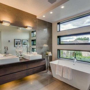 Foto på ett mellanstort funkis en-suite badrum, med släta luckor, skåp i mörkt trä, ett fristående badkar, en hörndusch, en toalettstol med separat cisternkåpa, vit kakel, vita väggar, bänkskiva i glas, klinkergolv i porslin och ett fristående handfat