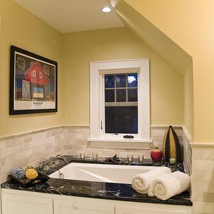 Idee per una stanza da bagno design con vasca sottopiano, piastrelle beige, piastrelle di marmo, pareti gialle, pavimento con piastrelle a mosaico e pavimento multicolore