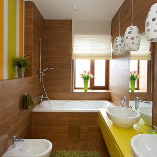 Example of an eclectic medium tone wood floor bathroom design in Other with a vessel sink, flat-panel cabinets, yellow cabinets, a bidet, brown walls and yellow countertops