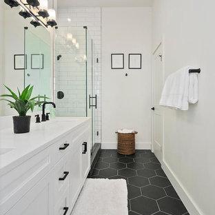 Idée de décoration pour une salle d'eau nordique avec un placard à porte shaker, des portes de placard blanches, un carrelage blanc, un carrelage métro, un mur blanc, un lavabo encastré, un sol noir, une cabine de douche à porte battante et un plan de toilette blanc.