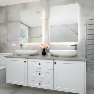 This is an example of a large beach style master bathroom in Sydney with shaker cabinets, white cabinets, gray tile, ceramic tile, ceramic floors, engineered quartz benchtops, grey floor, grey benchtops, a vessel sink and a double vanity.