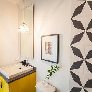 Kleines Modernes Duschbad mit flächenbündigen Schrankfronten, gelben Schränken, Wandtoilette mit Spülkasten, schwarz-weißen Fliesen, Keramikfliesen, weißer Wandfarbe, Betonboden, Einbauwaschbecken und Quarzit-Waschtisch in Austin