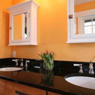 Exemple d'une salle de bain chic avec des portes de placard en bois brun et un mur orange.