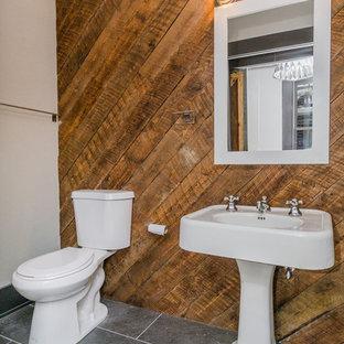 Ejemplo de cuarto de baño con ducha, industrial, de tamaño medio, con ducha empotrada, sanitario de dos piezas, baldosas y/o azulejos grises, paredes beige, suelo de pizarra y lavabo con pedestal