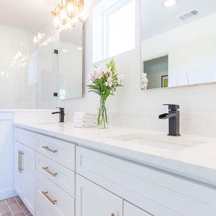 Foto de cuarto de baño principal, tradicional renovado, grande, con armarios estilo shaker, puertas de armario blancas, ducha empotrada, paredes blancas, suelo de ladrillo, lavabo bajoencimera y encimera de cuarzo compacto