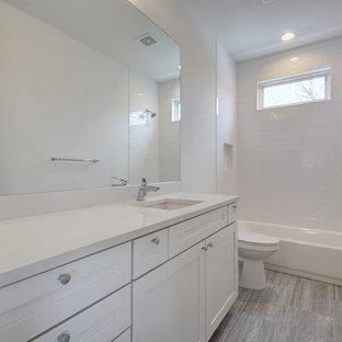 オースティンの中サイズのミッドセンチュリースタイルのおしゃれなバスルーム (浴槽なし) (シェーカースタイル扉のキャビネット、白いキャビネット、アルコーブ型浴槽、シャワー付き浴槽、分離型トイレ、白いタイル、サブウェイタイル、白い壁、ラミネートの床、アンダーカウンター洗面器、珪岩の洗面台、茶色い床、シャワーカーテン、白い洗面カウンター) の写真