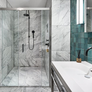 Inspiration for a medium sized contemporary ensuite bathroom in London with open cabinets, an alcove shower, a one-piece toilet, white tiles, marble tiles, blue walls, marble flooring, a console sink, solid surface worktops, white floors and a sliding door.