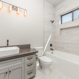 Ejemplo de cuarto de baño principal, contemporáneo, pequeño, con armarios con paneles lisos, puertas de armario grises, bañera empotrada, ducha empotrada, sanitario de una pieza, baldosas y/o azulejos grises, baldosas y/o azulejos de cerámica, paredes beige, suelo de mármol, lavabo integrado, encimera de mármol, suelo beige, ducha abierta y encimeras marrones