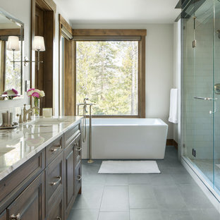 Freestanding bathtub - transitional master beige tile and white tile gray floor freestanding bathtub idea in Denver with raised-panel cabinets, brown cabinets, white walls, an undermount sink and a hinged shower door
