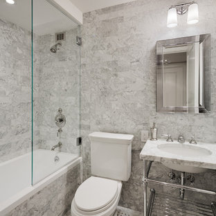 This is an example of a mid-sized transitional bathroom in New York with an alcove tub, a shower/bathtub combo, a two-piece toilet, gray tile, open cabinets, marble, grey walls, marble floors, a console sink and marble benchtops.