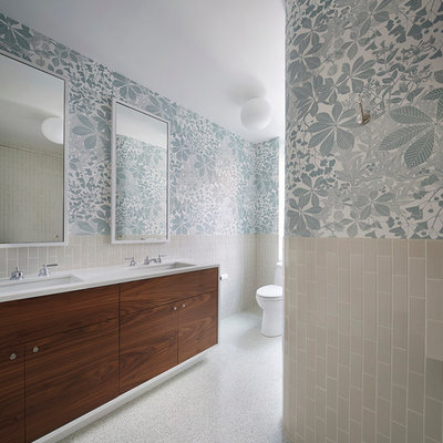 Example of a trendy beige tile and ceramic tile bathroom design in New York with flat-panel cabinets, dark wood cabinets, multicolored walls, an undermount sink, a one-piece toilet and solid surface countertops