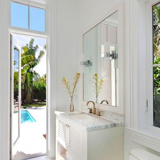 Diseño de cuarto de baño tradicional renovado con armarios con puertas mallorquinas, puertas de armario blancas y paredes blancas
