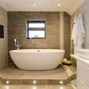 This is an example of a contemporary bathroom in Buckinghamshire with a vessel sink, flat-panel cabinets, white cabinets, a freestanding bath, beige tiles and beige walls.