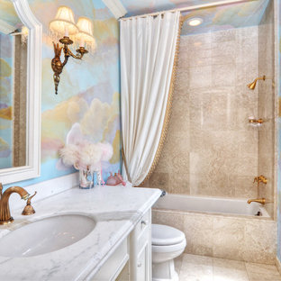 Medium sized mediterranean family bathroom in Orange County with white cabinets, marble worktops, a built-in bath, beige tiles, multi-coloured walls and travertine flooring.