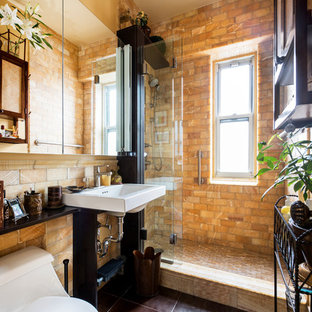 Example of a small tuscan stone tile and brown tile ceramic floor alcove shower design in New York with a two-piece toilet, multicolored walls and a wall-mount sink