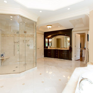 Elegant master ceramic floor bathroom photo in Boston with recessed-panel cabinets, dark wood cabinets, beige walls and a drop-in sink