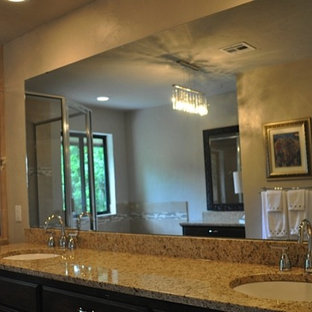 Inspiration for a mid-sized timeless master ceramic tile ceramic floor bathroom remodel in Oklahoma City with raised-panel cabinets, dark wood cabinets, a one-piece toilet, brown walls, an undermount sink and granite countertops
