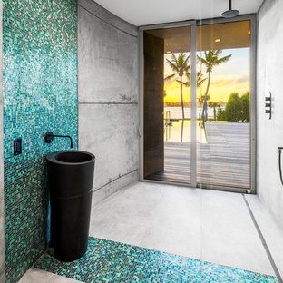 Example of a trendy blue tile and green tile concrete floor and gray floor bathroom design in Miami with gray walls, a console sink and black countertops