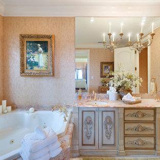 Создайте стильный интерьер: главная ванная комната в классическом стиле с фасадами островного типа, бежевыми фасадами, гидромассажной ванной, бежевыми стенами, врезной раковиной и красной столешницей - последний тренд