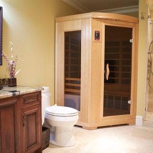 Esempio di una stanza da bagno mediterranea con lavabo sottopiano, ante con bugna sagomata, ante in legno scuro, top in granito, doccia aperta, WC monopezzo, piastrelle in pietra e pavimento in pietra calcarea