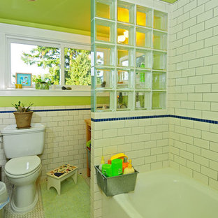 Photo of a small classic family bathroom in Seattle with a console sink, an alcove bath, a shower/bath combination, a two-piece toilet, white tiles, metro tiles, green walls and ceramic flooring.
