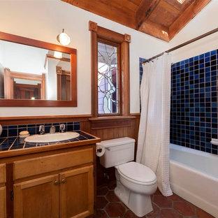 На фото: ванная комната в стиле современная классика с накладной раковиной, душем над ванной, столешницей из плитки, шторкой для душа и синей столешницей с