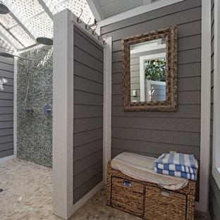 Beach style pebble tile floor and beige floor bathroom photo in Miami with gray walls