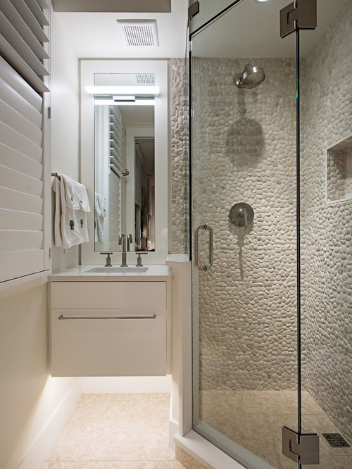 Example of a coastal gray tile and pebble tile beige floor corner shower  design in Miami