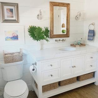 Foto på ett mellanstort maritimt vit badrum med dusch, med luckor med infälld panel, vita skåp, en toalettstol med separat cisternkåpa, vita väggar, ett undermonterad handfat och beiget golv
