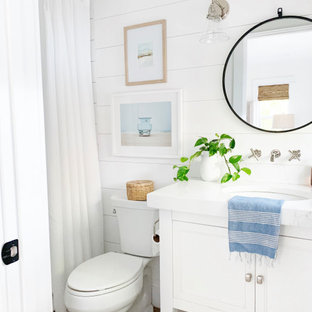 Example of a mid-sized beach style 3/4 beige floor, single-sink and shiplap wall bathroom design in Orlando with recessed-panel cabinets, white cabinets, a two-piece toilet, white walls, an undermount sink, white countertops and a built-in vanity