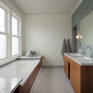 Inspiration for a contemporary gray tile and subway tile mosaic tile floor bathroom remodel in San Francisco with an undermount sink, flat-panel cabinets, medium tone wood cabinets, an undermount tub and gray countertops