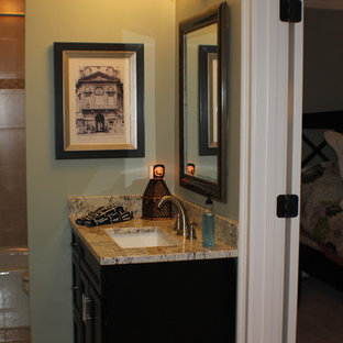 Small trendy travertine floor bathroom photo in Atlanta with shaker cabinets, black cabinets, blue walls, an undermount sink and granite countertops