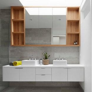 Ispirazione per una stanza da bagno padronale scandinava di medie dimensioni con lavabo a consolle, ante lisce, ante bianche, top in quarzo composito, piastrelle grigie, piastrelle in pietra, pareti grigie e pavimento in cemento