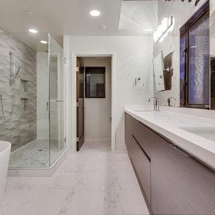 Imagen de cuarto de baño principal, actual, grande, con lavabo bajoencimera, armarios con paneles lisos, puertas de armario de madera clara, encimera de cuarzo compacto, bañera exenta, combinación de ducha y bañera, sanitario de una pieza, baldosas y/o azulejos con efecto espejo, paredes blancas y suelo de mármol
