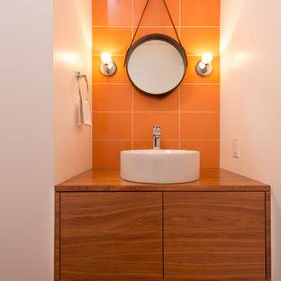 Idéer för att renovera ett litet funkis badrum med dusch, med ett fristående handfat, släta luckor, skåp i mörkt trä, träbänkskiva, orange kakel, porslinskakel, vita väggar och ljust trägolv