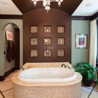 Modelo de cuarto de baño clásico con encimera de mármol, bañera encastrada y baldosas y/o azulejos beige