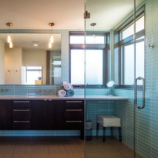 Modelo de cuarto de baño principal, contemporáneo, de tamaño medio, con armarios con paneles lisos, puertas de armario negras, ducha esquinera, baldosas y/o azulejos azules, baldosas y/o azulejos de vidrio, paredes azules, suelo de bambú, lavabo integrado, suelo marrón, ducha con puerta con bisagras y encimeras blancas