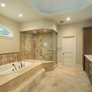 Inredning av ett klassiskt stort en-suite badrum, med luckor med infälld panel, skåp i mörkt trä, ett platsbyggt badkar, en hörndusch, beige kakel, travertinkakel, beige väggar, travertin golv, marmorbänkskiva, beiget golv och dusch med gångjärnsdörr