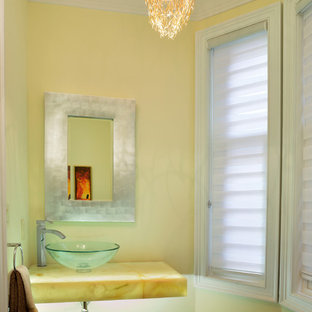 Bild på ett funkis gul gult badrum, med ett fristående handfat, bänkskiva i onyx och gula väggar