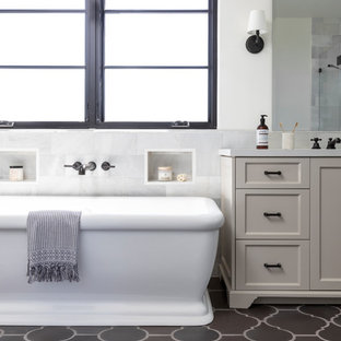 Tuscan white tile brown floor freestanding bathtub photo in Los Angeles with shaker cabinets, beige cabinets, white walls and white countertops