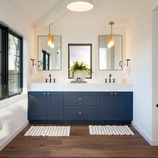 Idee per una stanza da bagno classica con ante in stile shaker, ante blu, pareti bianche, parquet scuro, pavimento marrone e top bianco