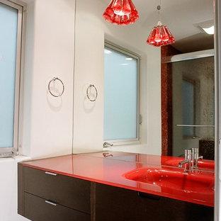 Идея дизайна: ванная комната в современном стиле с монолитной раковиной, плоскими фасадами, темными деревянными фасадами и красной столешницей
