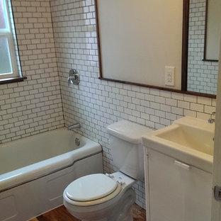 Foto di una stanza da bagno stile americano con lavabo rettangolare, ante turchesi, vasca da incasso, vasca/doccia, WC monopezzo, piastrelle bianche, piastrelle in ceramica, pareti bianche e pavimento in legno massello medio